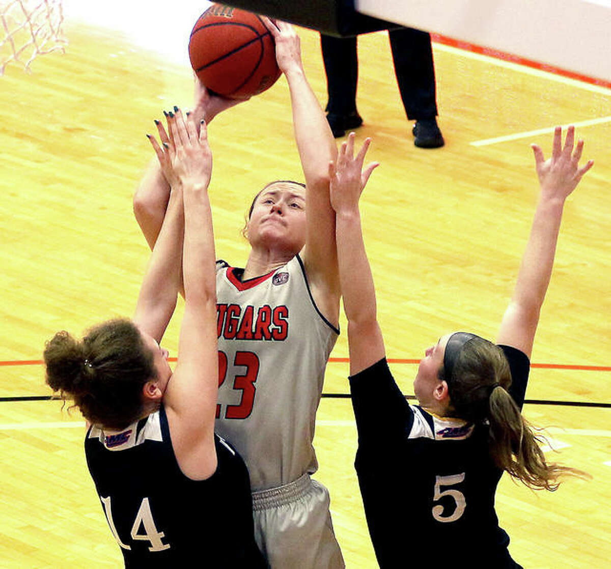 SIUE senior Allie Troeckler shoots over a pair of Health Sciences and Pharmacy defenders during Wednesday's home opener at First Community Arena in Edwardsville. The Cougars are back at home Saturday afternoon against Kansas City.