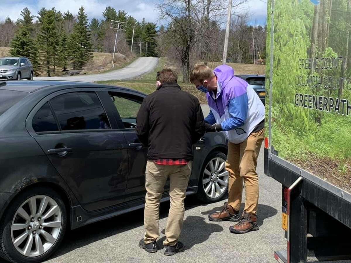 Daniel Ward, the transportation and outreach coordinator for Greener Pathways, an organization that provides mobile addiction services, and Kyle Buono, a peer advocate with the organization, conduct a drive-up Narcan training during the COVID-19 pandemic for a community member in Tannersville, N.Y.