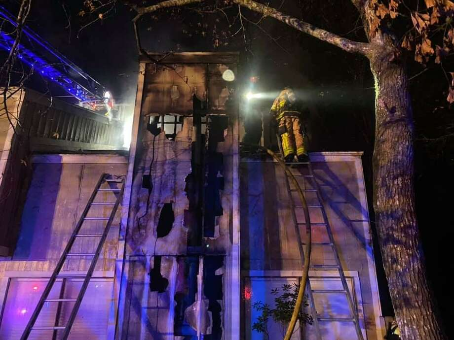 """The Woodlands Fire Department firefighters are seen in December 2020 after ending a chimney blaze at a home in Grogan's Mill Village. The Montgomery County Fire Marshal's Office is warning residents about these next three months being """"peak"""" season for home heating fires. Photo: Courtesy Of The Montgomery County Fire Marshal's Office"""