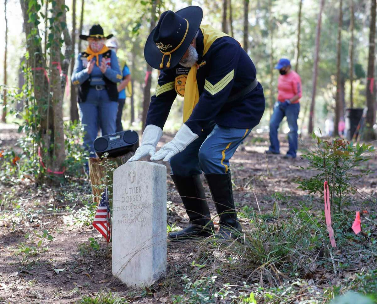 Billy Ray Smith, a member of the National Association of Buffalo Soldiers, touches the headstone of Luther Dorsey, the only known Buffalo Solider in Montgomery County, during a sign dedication for the Conroe Community Cemetery, Saturday, Nov. 7, 2020, in Conroe. The Conroe Community Cemetery Restoration Project has lead efforts to restore the site, which dates back to the 1890s and includes emancipated slaves, railroad workers, saw mill workers and the only confirmed Buffalo Solider buried in Montgomery County.