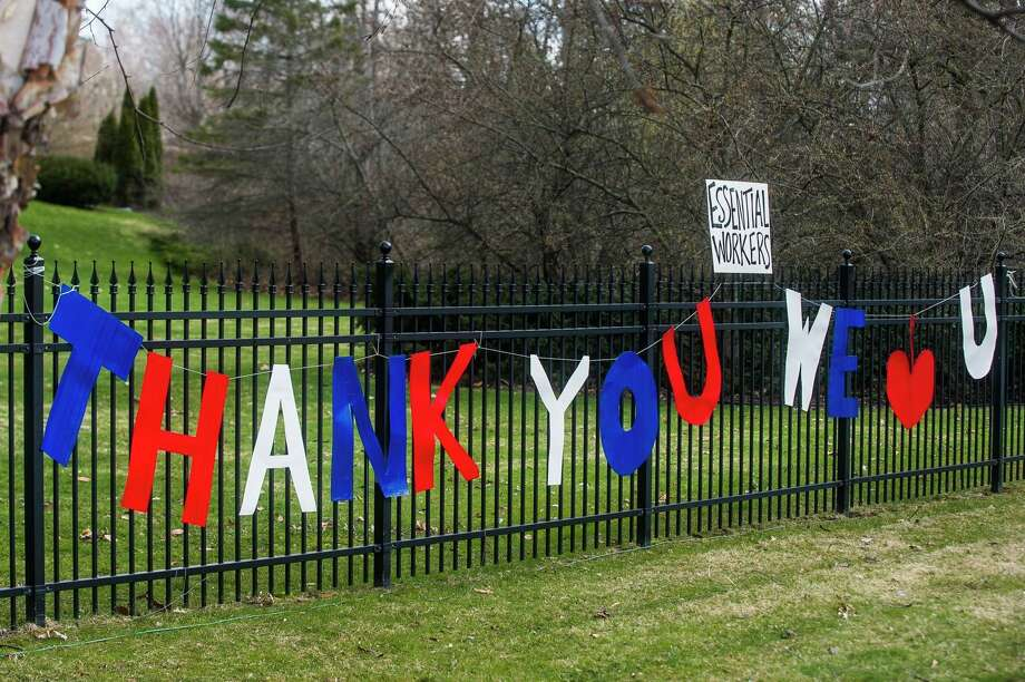 Signs thanking essential workers are displayed Wednesday, April 15, 2020 outside of homes along Sugnet Road, where hospital employees may see them on their way to work. (Katy Kildee/kkildee@mdn.net)