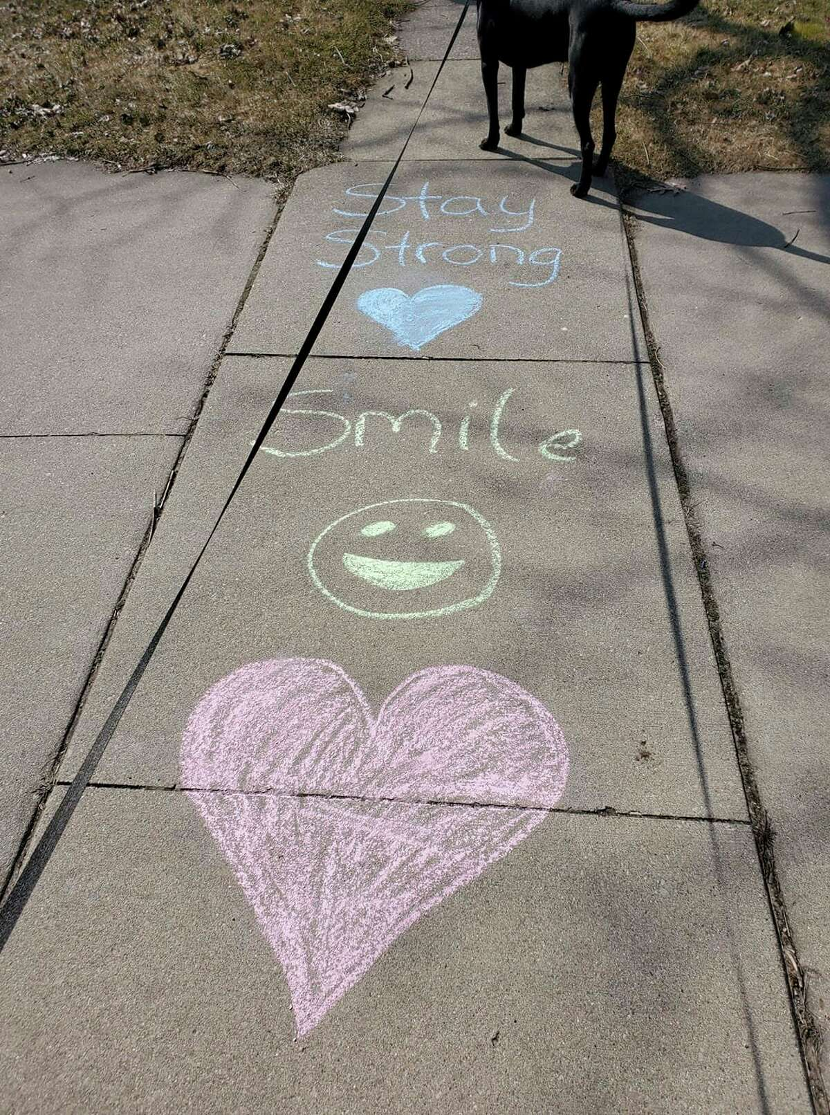 Positive messages are written on the sidewalk in chalk, part of a movement called Chalk Your Walk that gained momentum via social media to spread cheer in the neighborhood as people were socially distancing. (Photo provided/Julie A. Yahr)