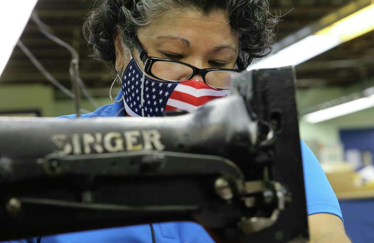 Seamstress Lucy Rodriguez wears a patriotic mask while she sews the red and white stripes for a U.S. flag on a trusty Singer sewing machine at Dixie Flag and Banner Company.