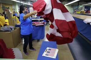 Rodriguez unfurls the red and white portion of a flag that she stitched.