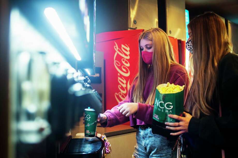 Keeley Rogers, 17, center, and Abbey Anglin, 17, right, stop to get concessions before watching a movie Friday, Oct. 9, 2020 at Midland Cinemas, the first day the theater has reopened in several months. (Katy Kildee/kkildee@mdn.net)