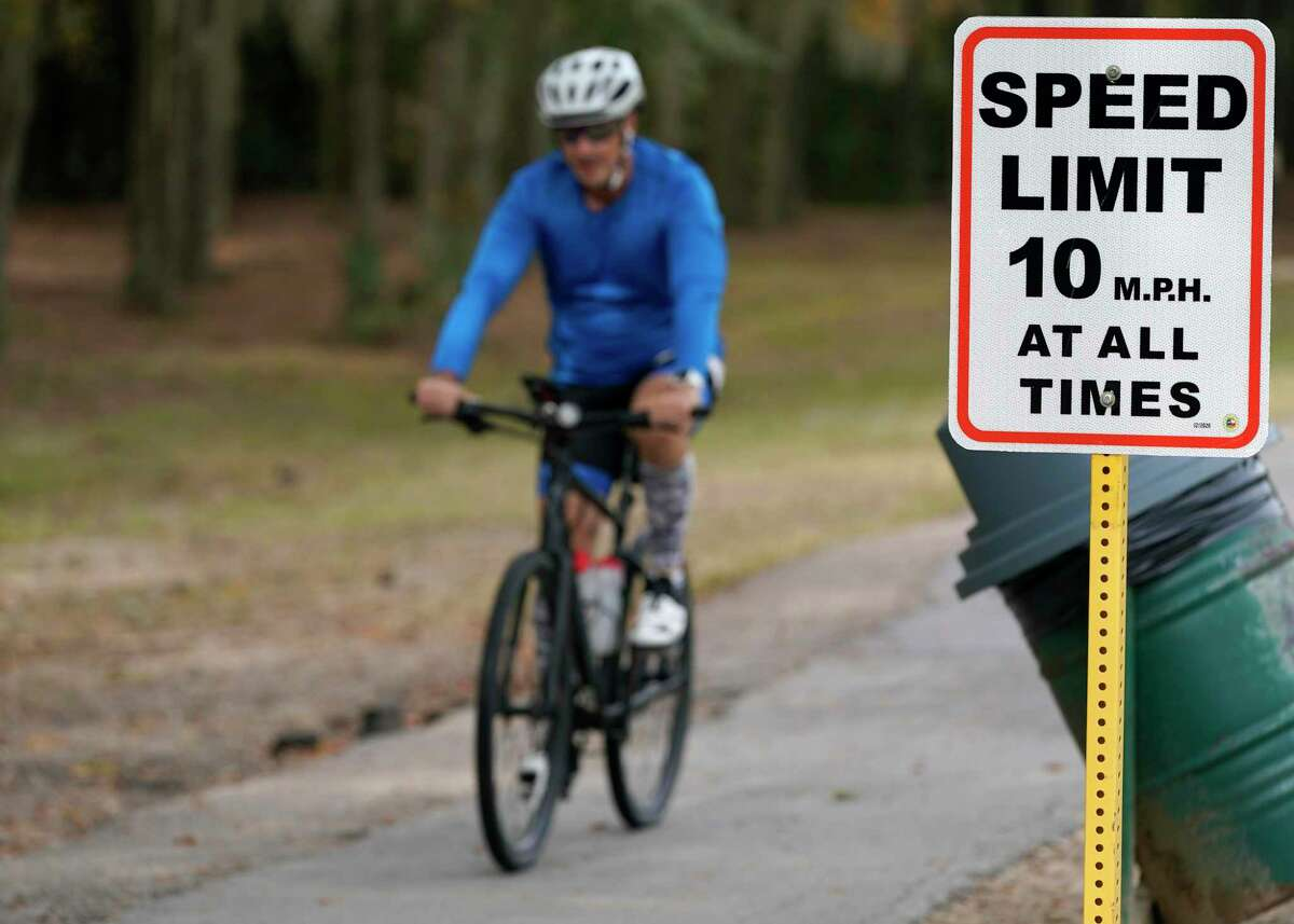 A bicyclist rides past a speed limit sign in Terry Hershey Park on Dec. 11, 2020 in Houston. Precinct 3 installed speed limit signs in George Bush and Terry Hershey Park and says they will enforce them for the trails. The 10 mph speed limits are needed, county officials said, because of complaints about cyclists on park pathways where there is pedestrian activity.