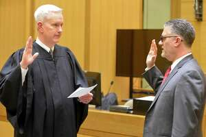Supreme Court Associate Justice Andrew J. McDonald, left, administered the oath of office last year to Richard Colangelo Jr., the chief state's attorney.