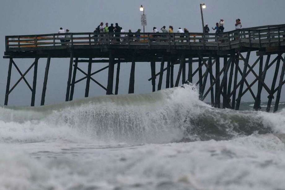 KILL DEVILL HILLS, NC - SEPTEMBER 02:  People stand on the Avalon Fishing Pier watching the heavy surf from approaching Hurricane Earl, on September 2, 2010 in Kill Devil Hills, North Carolina. A hurricane warning has been issued for most of the North Carolina coastline due to the approaching Category 3 Hurricane Earl that is expected to pass the Outer Banks of North Carolina late tonight and into the morning.  (Photo by Mark Wilson/Getty Images) Photo: Mark Wilson, Getty Images / 2010 Getty Images