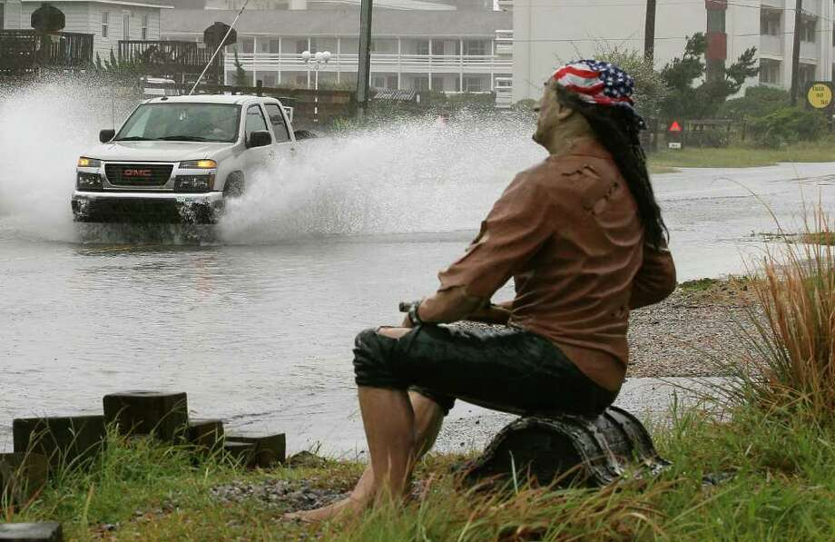 KILL DEVIL HILLS, NC - SEPTEMBER 03:  A truck travels down a water covered beach road in front of a resturant statue, on September 3, 2010 in Kill Devil Hills, North Carolina. Hurricane Earl was downgraded to a category 2 before brushing the Outer Banks early Friday morning causing minimal damage.  (Photo by Mark Wilson/Getty Images) Photo: Mark Wilson, Getty Images / 2010 Getty Images
