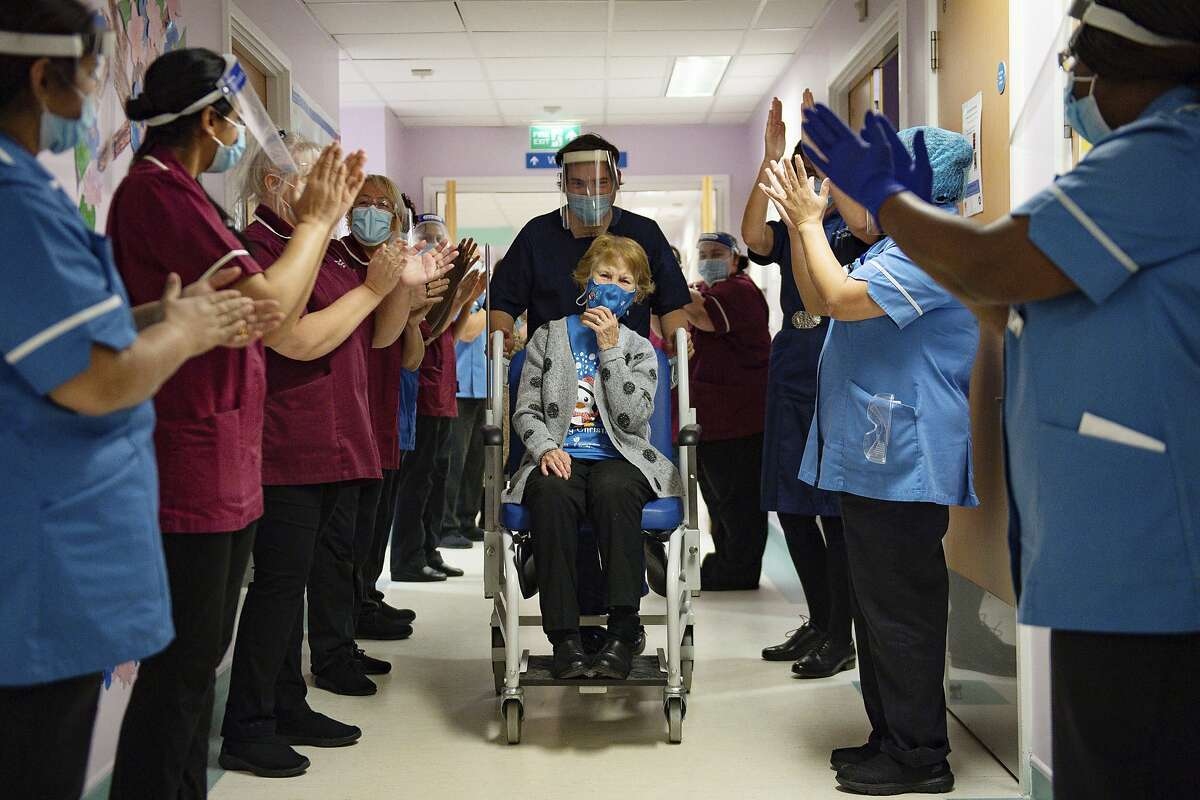Margaret Keenan, 90, is applauded by staff as she returns to her ward after becoming the first patient in the UK to receive the Pfizer-BioNTech COVID-19 vaccine, at University Hospital, Coventry, England, Tuesday Dec. 8, 2020.