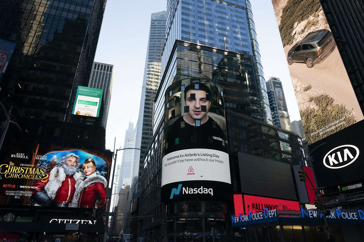 Brian Chesky, CEO of Airbnb, is shown on an electronic screen, center, at the Nasdaq MarketSite, Thursday, Dec. 10, 2020, in New York. The San Francisco-based online vacation rental company holds its IPO Thursday. (AP Photo/Mark Lennihan)