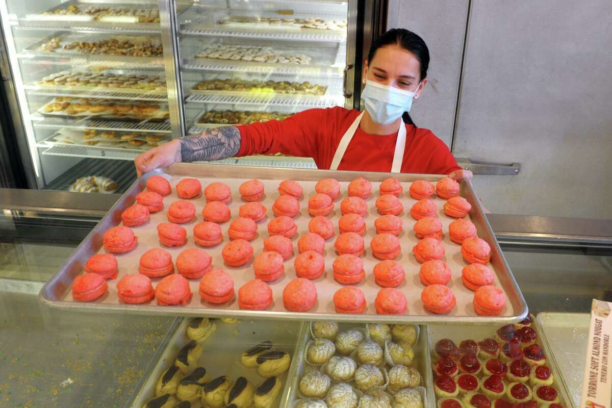 Kate Webber brings out a tray of French macaroons at Angela Mia Italian Bakery, in Norwalk, Conn. Dec. 10, 2020. The bakery opened fifty years ago in December of 1970. Like many Fairfield County shops, Angela Mia Italian Bakery has gotten its share of famous customers, in its case to include Kirk Douglas, Paul Newman and Tom Selleck. The bakery reaches the half-century milestone on Saturday, Dec. 19, the date in 1970 when Joe Agoglia opened the shop still located today at 247 Connecticut Ave. Signs lining the roadway back then including Caldor, Old McDonald's Farm and Swanky Franks. Angela Mia is the third-generation iteration of the original Premiata Pastry opened in Brooklyn by Luigi DelPrete and a second shop opened by his daughter Cristina and spouse Pasquale Agoglia who had worked there since the age of nine. Their son Joe named the Norwalk bakery after daughter Angela, whose own eldest daughter Cristina continues to help out after having graduated from the University of Connecticut and now pursuing a master's degree in business.