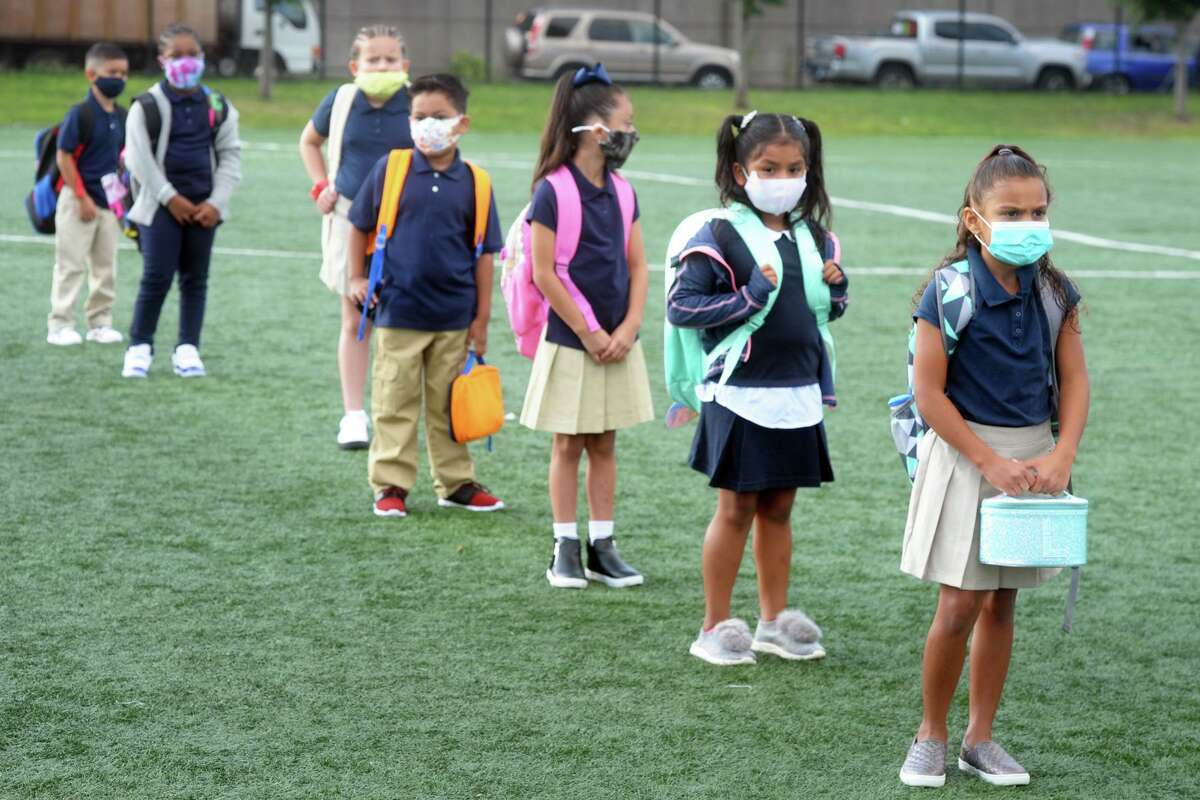 Students line up at a safe social distance prior to entering Roosevelt School for the first days of class, in Bridgeport, Conn. Sept. 8, 2020.