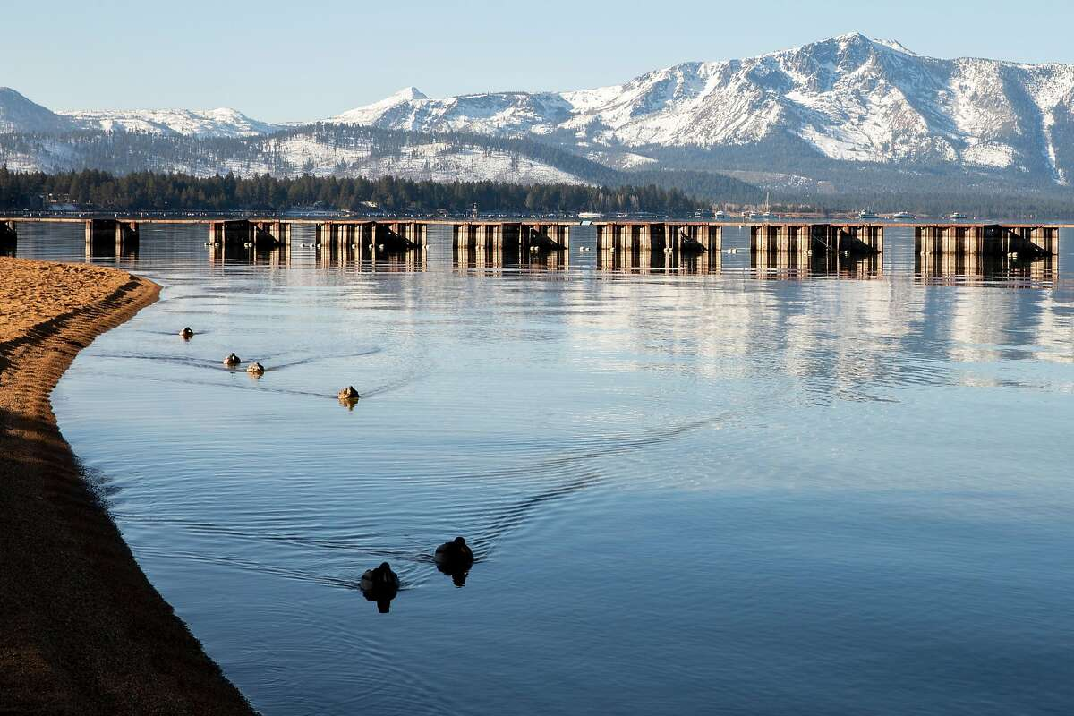 Ducks glide across glassy waters as mountains dusted in snow are seen in South Lake Tahoe on Dec. 10 as the region was about to fall under a ban on vacation travel due to a rise in the number of COVID-19 hospitalizations.
