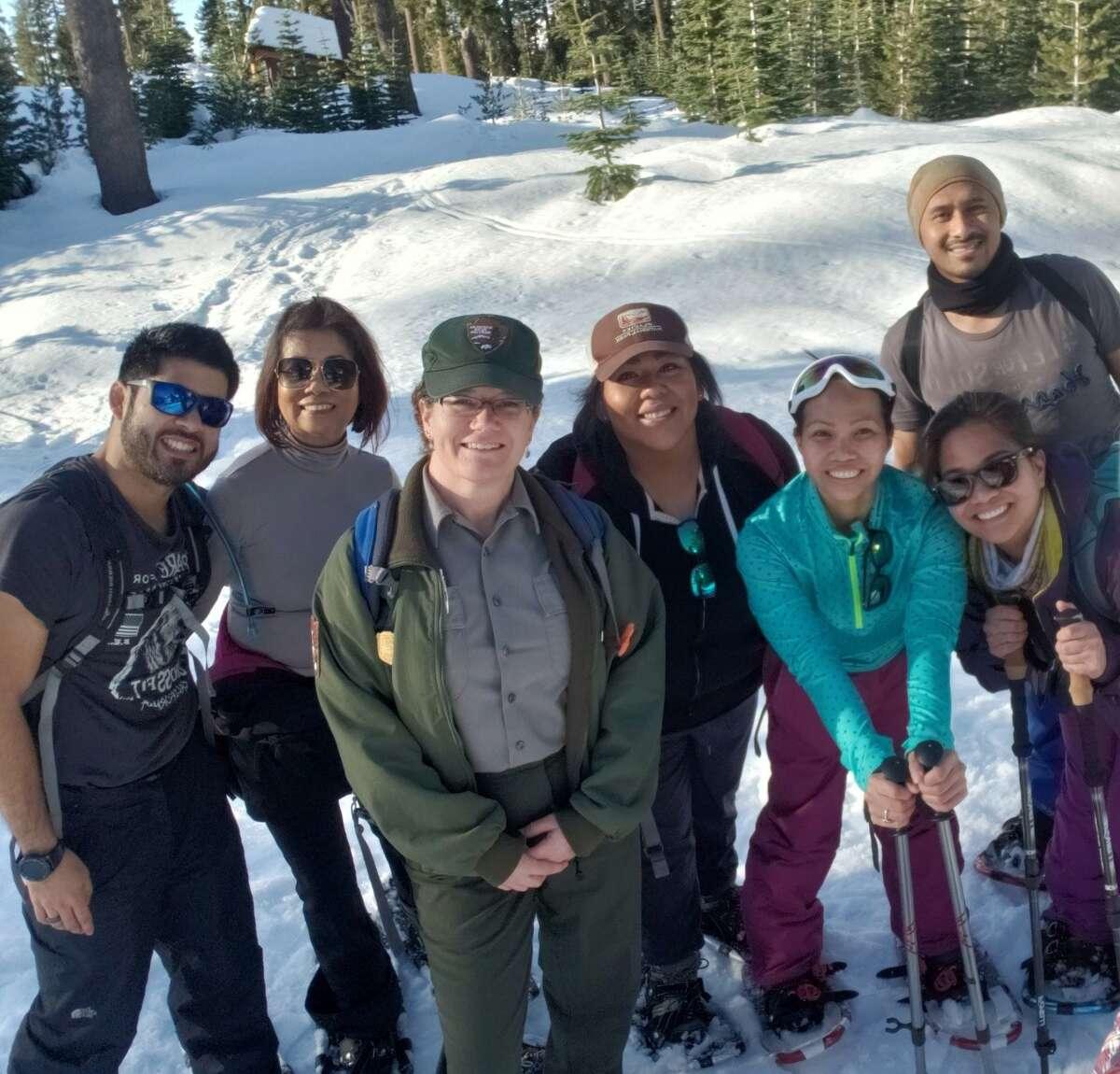 Park ranger Shanda Ochs and group of snowshoe walk participants outside of the Kohm yah-mah-nee Visitor Center.