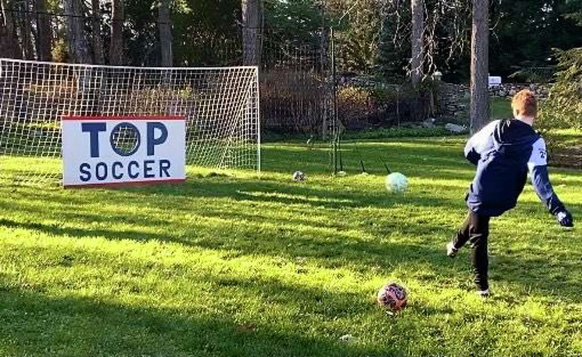 Bruno Guiduli in his front yard Thursday afternoon. Guiduli is raising money to raise awareness for TOPSoccer, a nonprofit focusing on working with children with intellectual and physical disabilities through soccer.