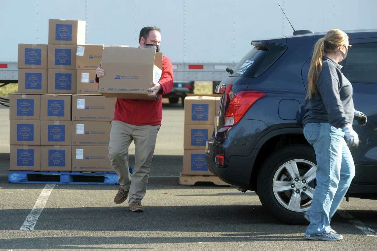 Volunteers load boxes of food into passing cars during TEAM INC's drive-thru food donation in the parking lot of Nolan Field, in Ansonia, Conn. Dec. 11, 2020.