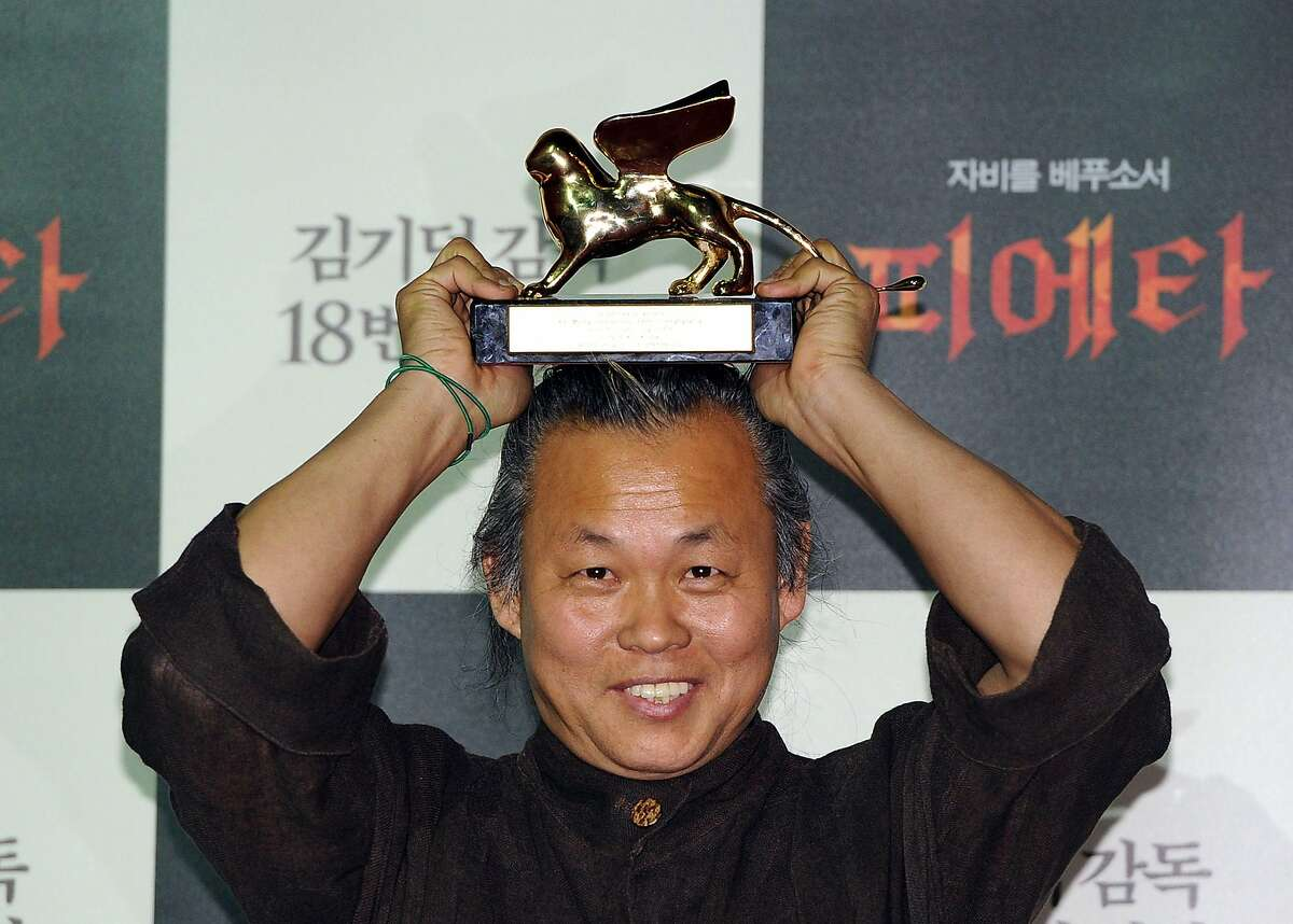 (FILES) In this file photo taken on September 11, 2012, South Korean director Kim Ki-Duk poses with the Golden Lion for Best Film during a press conference in Seoul after he won the best film award at the Venice film festival with