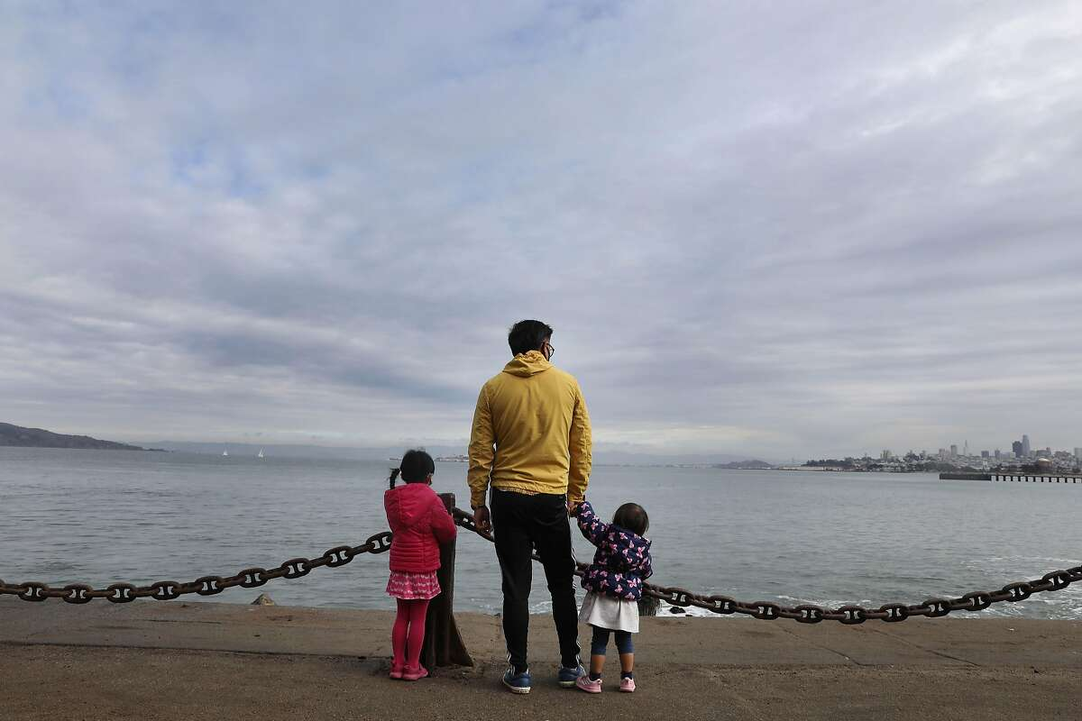 Demos Wong of Burlingame and daughters Lyndia (left) and Sinaya take in the view of the bay under a cloudy sky at Fort Point in San Francisco.