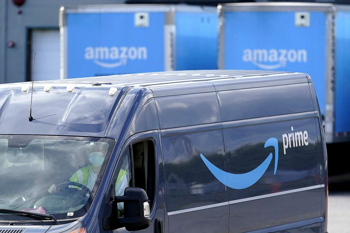 In this Oct. 1, 2020 file photo, an Amazon Prime logo appears on the side of a delivery van as it departs an Amazon Warehouse.