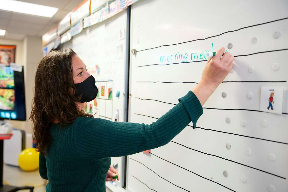 Cindy Evans, a middle school special education teacher, sets up her classroom board at her classroom at San Jose Middle School in Novato.