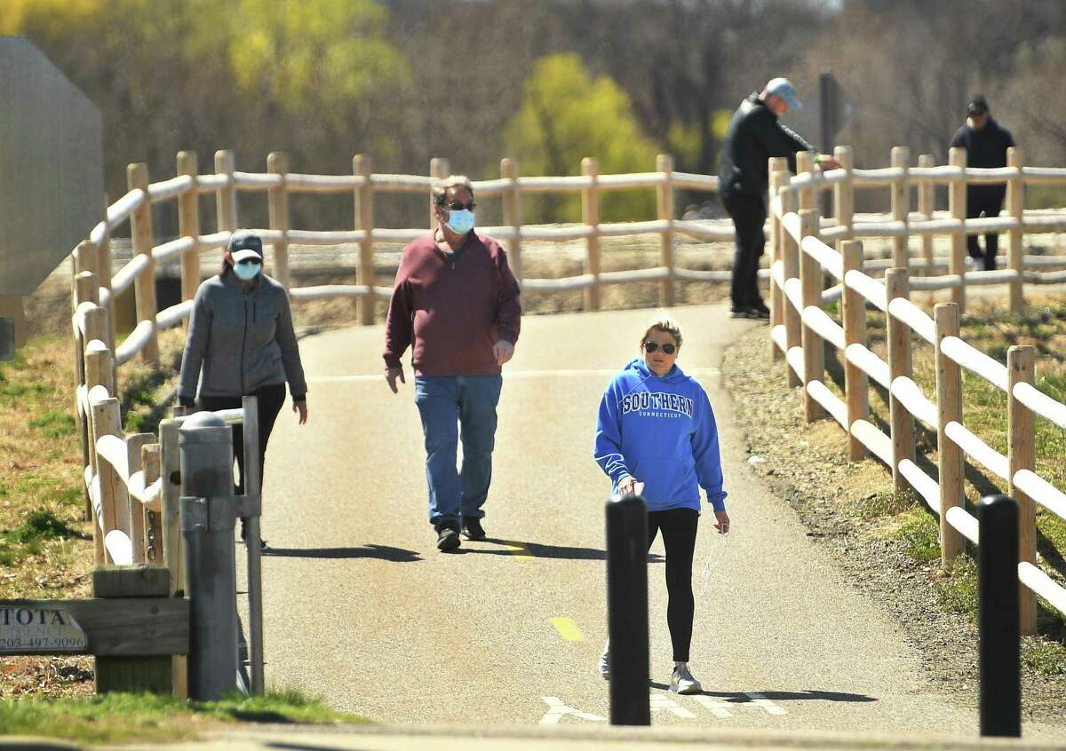 Walkers enjoy the sunny weather on the Derby Greenway section of the Naugatuck River Greenway in Derby, Conn. on Monday, April 6, 2020. The Ansonia section of the Greenway, called the Ansonia Riverwalk, has been closed due to social distancing concerns during the coronavirus pandemic. Members of the Northwest Hills Council of Governments endorsed the completed Naugatuck River Greenway Thomaston to Torrington Routing Feasibility Study Report this week, taking another step toward providing residents with a recreational opportunity for the future.