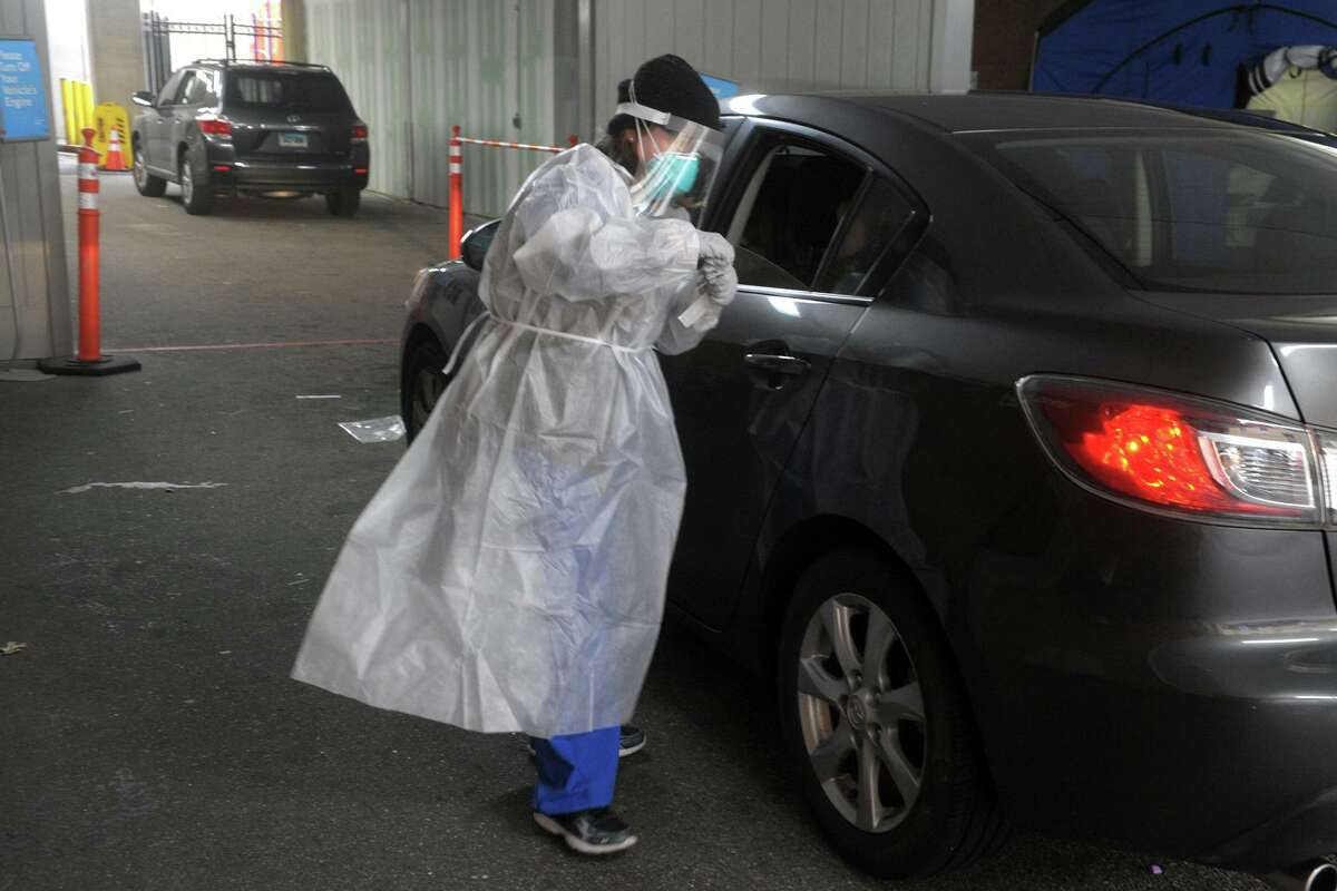 Medical personnel conduct the daily drive-thru COVID-19 testing at Bridgeport Hospital on Dec. 9.
