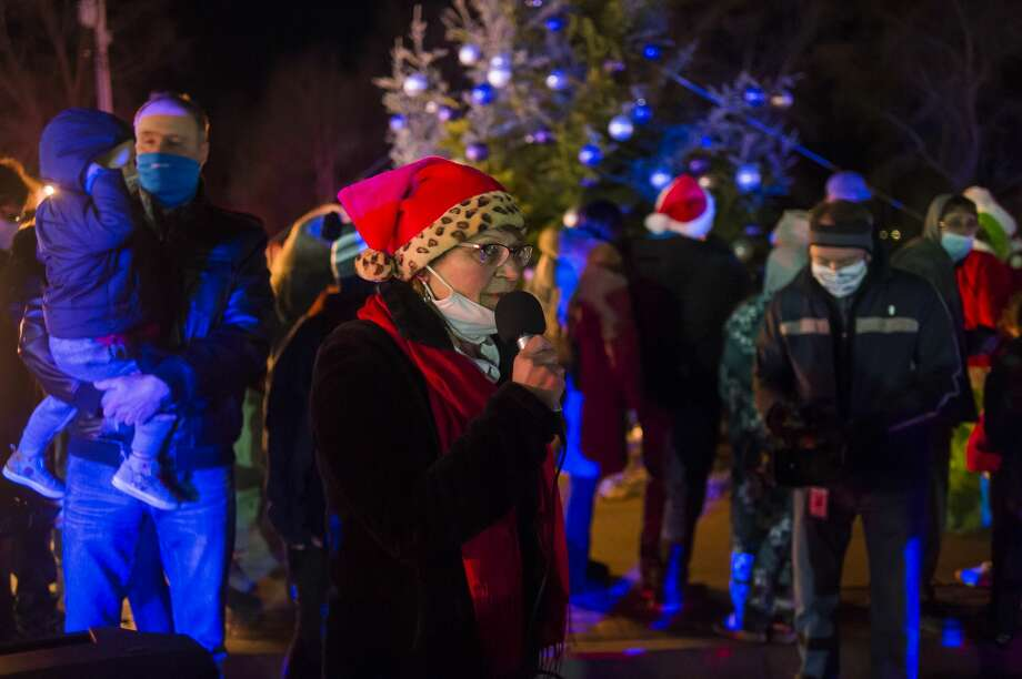 Sanford Village President Dolores Porte speaks to a crowd before before the Christmas tree is lit while hundreds of vehicles line up to view the Sanford Lit Christmas Tree Memorial, which features over 60 decorated trees in the area south of the rail trail, Friday, Dec. 11, 2020 in downtown Sanford. (Katy Kildee/kkildee@mdn.net) Photo: (Katy Kildee/kkildee@mdn.net)