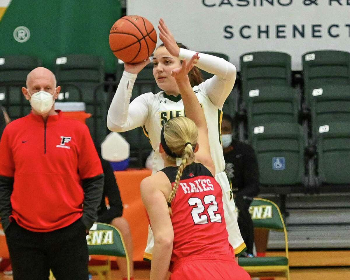 Siena College junior Margo Peterson takes a jumper over Fairfield University Rachel Hakes while Fairfield coach Joe Frager looks on during the Metro Atlantic Athletic Conference season opener at Siena College in Loudonville, NY, on Friday, Dec. 11, 2020 (Jim Franco/special to the Times Union.)
