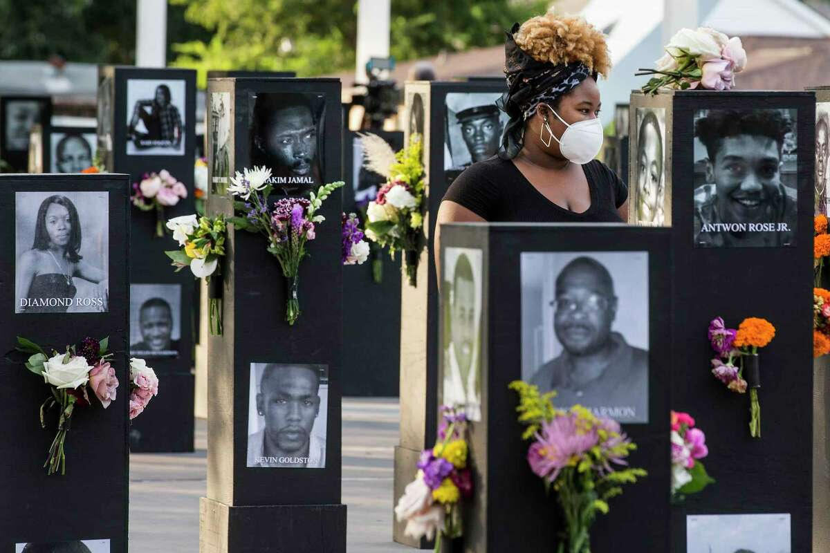 People walk through the Say Their Names Memorial in Emancipation Park on Monday, Sept. 28, 2020 in Houston. Brought to Houston by rap artist and activist Trae Tha Truth and Say Their Names, the memorial is dedicated to those who have lost their lives due to racial injustice. More than 200 photos, including George Floyd, Breonna Taylor, Dr. Martin Luther King, Jr., and Emmett Till to name a few, are featured.