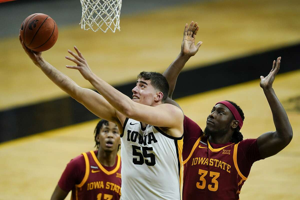 Iowa center Luka Garza drives to the basket ahead of Iowa State forward Solomon Young (33) during the second half of an NCAA college basketball game, Friday, Dec. 11, 2020, in Iowa City, Iowa. Iowa won 105-77. (AP Photo/Charlie Neibergall)