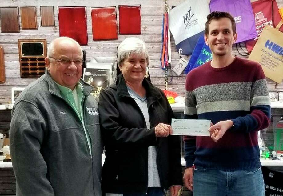 Accepting a donation check from Josh Tschirhart, Thumb Office Supply (right) is Sue Vaughan, Bad Axe Senior Retiree Club (center) member. Also pictured is Dan Glaza of Bad Axe Senior Retiree Club-President. (Submitted Photo)