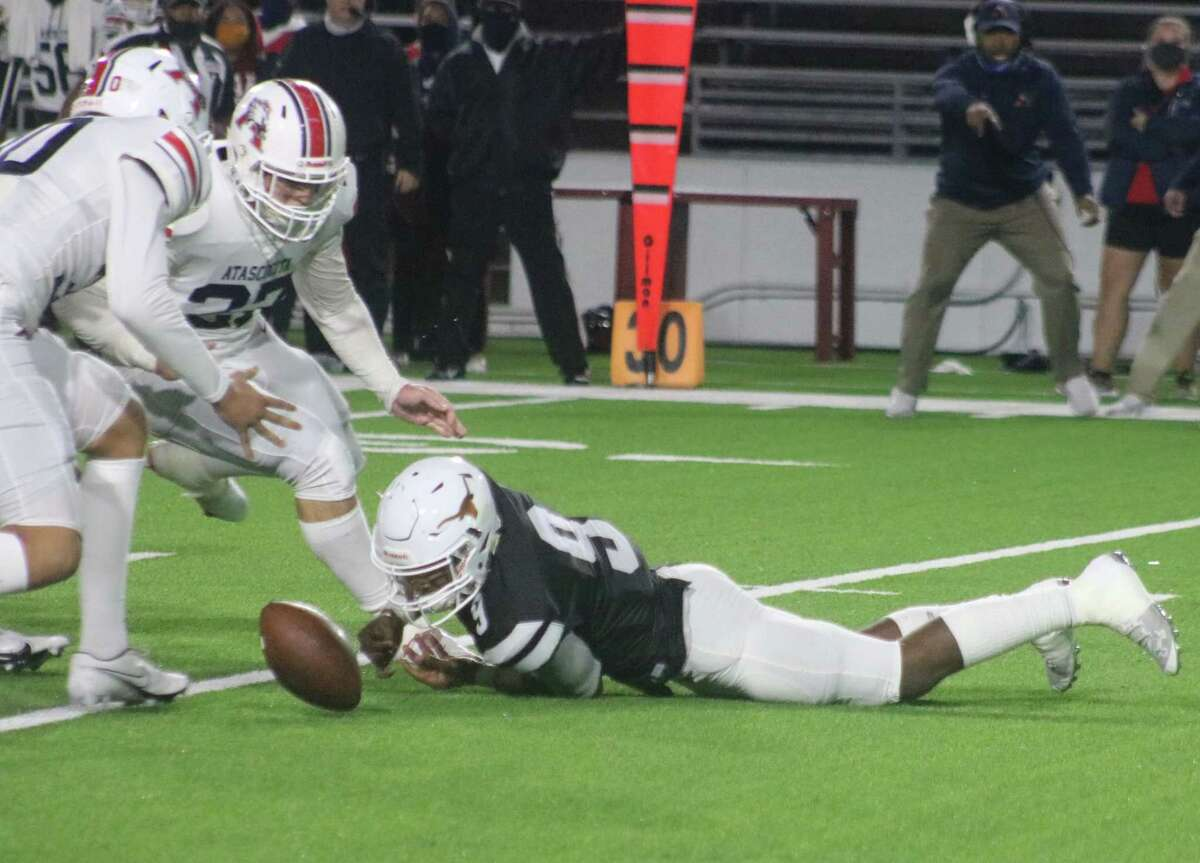 Dobie quarterback Cameron Gray tries to recover this fumble before an on-rushing Atascocita bunch does. Gray did, but it resulted in a 13-yard loss. A high snap from center caused the fumble.