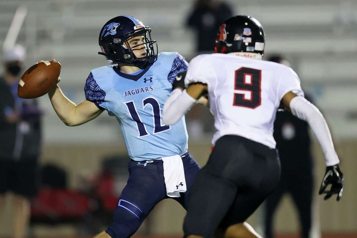 Johnson quarterback Ty Reasoner, left, looks to pass a Wagner's Terrance Hood applies pressure during the first half of their Class 6A, Division II first round high school football playoff at Comalander Stadium on Friday, Dec. 11, 2020.
