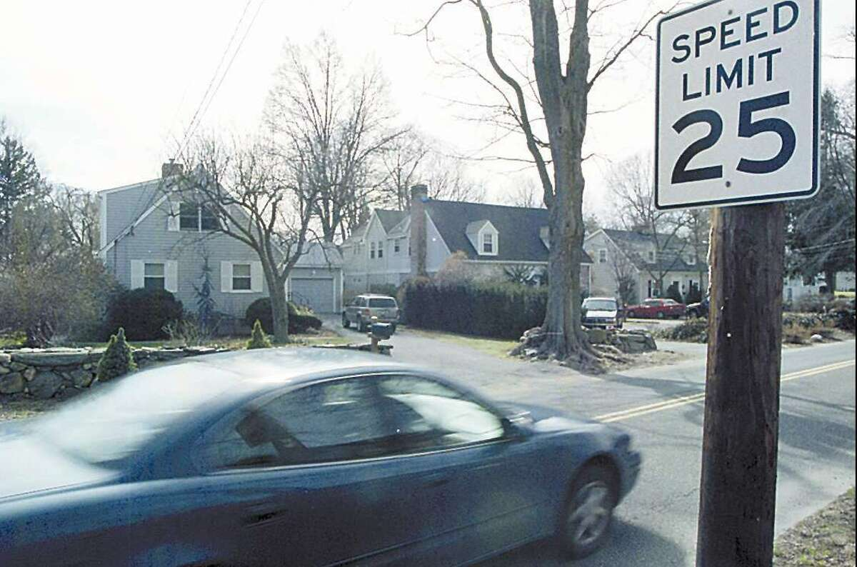 A car passes by speed limit sign on Lockwood Avenue near intersection of Tomac Avenue.
