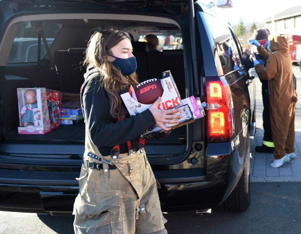 Darien junior Maya Patrosz collects donations at the Christmas car parade at Darien High School in Darien, Conn. Sunday, Dec. 6, 2020. Darien's three fire departments held a holiday drive-thru for cars featuring fire trucks and an appearance by Santa Claus. Donations for Toys for Tots and Person to Person were also collected at the event.