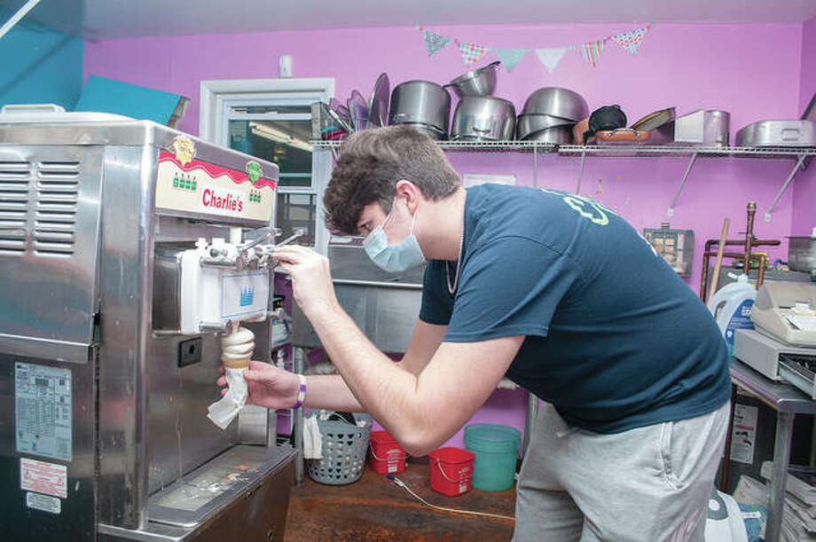 R.J. Grojean, 17, focuses on his work Friday at Charlie's Ice Cream Shop, 115 W. Lafayette Ave. With temperatures in the 40s just more than a week away from winter, a customer was in the mood for an icy-cold cone. Photo: Darren Iozia | Journal-Courier