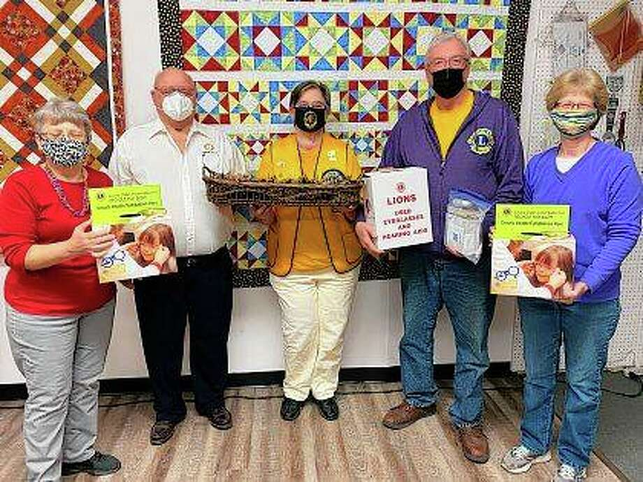 """Sue Fox (left) of Times Square Sewing Complex and Pam Farmer (right) of Sew Sweet Quilt Shop present donations of used eyeglasses and hearing aids to Fred Roberts (second from left) of Franklin Lions Club and Susan Nolls and Tom Atkins of Jacksonville Lions Club. The eyeglasses and hearing aids — only a portion of which are pictured — were collected during the annual Central Illinois Quilt Shop Hop, in which Times Square, Sew Sweet and 13 other quilt shops in the region participated. The shop hop's theme was """"Double Vision."""" A monetary donation also was made."""