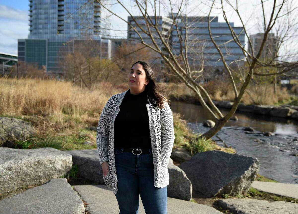 Stamford resident Samantha Chiafalo poses at Mill River Park in Stamford, Conn. on Tuesday, Dec. 8, 2020. Chiafalo noticed the stone while walking her dog through the park and has launched a petition calling for the Mill River Park Collaborative to remove the stone and denounce the company.
