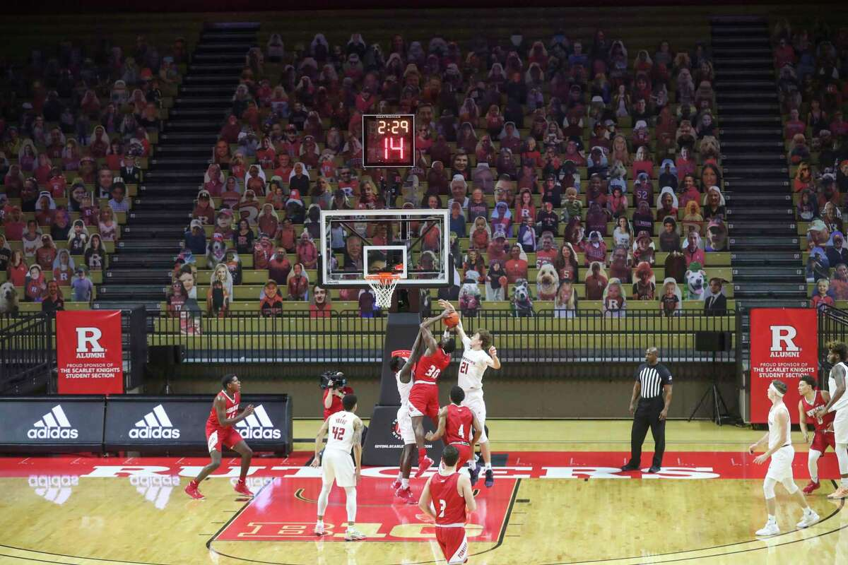 The empty student section, with cardboard cutouts of fans, is in the background as Rutgers forward Dean Reiber (21) blocks a shot by Sacred Heart forward Cantavio Dutreil (30) during the second half of an NCAA college basketball game Wednesday, Nov. 25, 2020, in Piscataway, N.J. (Andrew Mills/NJ Advance Media via AP)