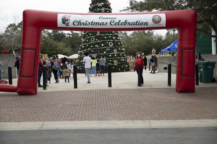 "Visitors walk in-and-out of the annual Toby Powell Conroe Christmas Celebration, Saturday, Dec. 12, 2020, in Conroe. This year featured two ""snow hills"", face painting, a petting zoo, a live nativity scene and more. Photo: Gustavo Huerta/Staff Photographer / 2020 © Houston Chronicle"