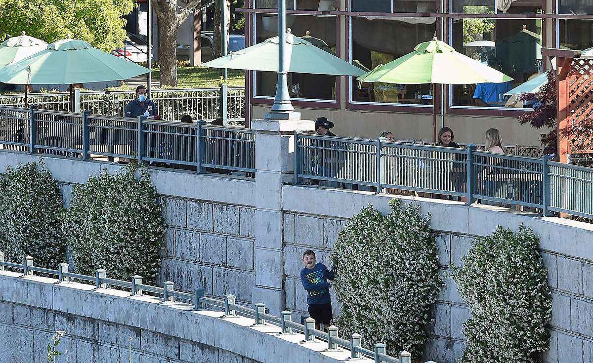 A boy plays below Downtown Joe's outdoor dining and bar in Napa. Napa advanced to the yellow tier, the least restrictive, of California's reopening blueprint for the final week before the entire state does away with the tier system.