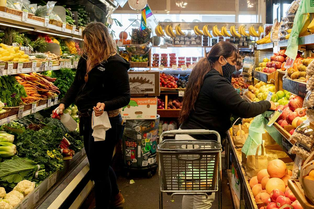 Angela Douglas (left) restocks produce as customers shop at Bi-Rite Market in the Mission District of San Francisco, Calif. Friday, November 20, 2020. With rising COVID cases, retailers, including grocers, are wary of surging crowds, and possible panic shopping not seen since March, over the holiday seasons.