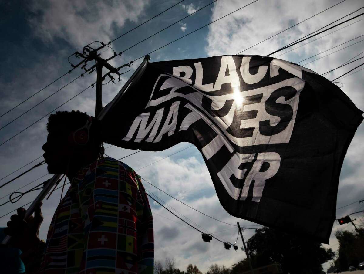 MD Crawford carries a Black Lives Matter flag before a march in La Marque, Texas on Saturday, Dec. 12, 2020, to protest the shooting of Joshua Feast, 22, by a La Marque police officer. Officials say Officer Jose Santos fatally shot Feast late Wednesday. (Stuart Villanueva /The Galveston County Daily News via AP)
