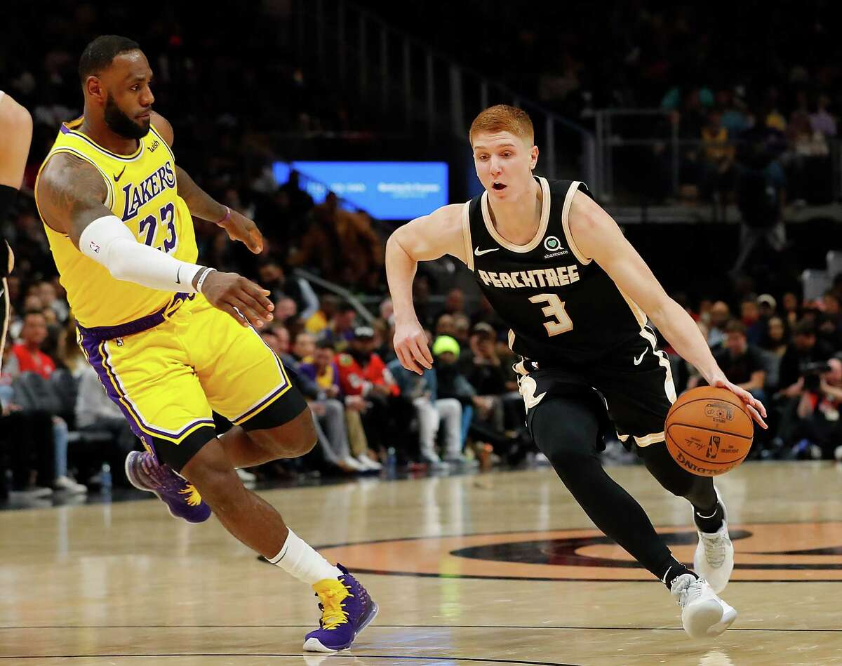 Kevin Huerter, right, of the Atlanta Hawks drives against LeBron James of the Lakers in 2019. Huerter is having a basketball event in Clifton Park on Saturday.