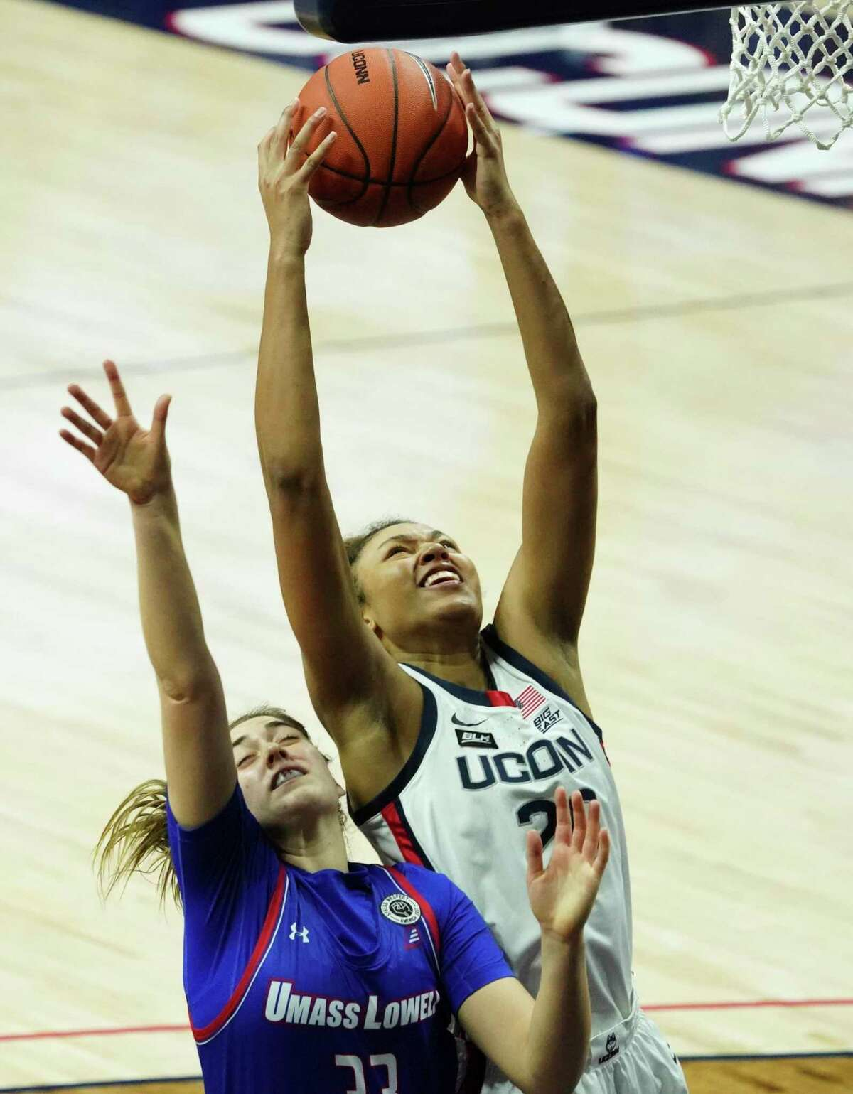 UConn forward Olivia Nelson-Ododa (20) grabs a rebound over UMass-Lowell forward Tiahna Sears (33) during second first half of an NCAA women's basketball game on Saturday in Storrs, Conn.