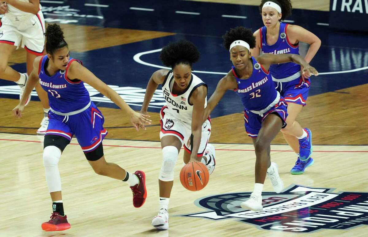 Connecticut guard Christyn Williams (13) drives the ball upcourt against UMass-Lowell guards Shamyjha Price (32) and Kaylen Banwareesingh (13)during the first half of an NCAA college basketball game, Saturday, Dec. 12, 2020, in Storrs, Conn. (David Butler II/Pool Photo via AP)