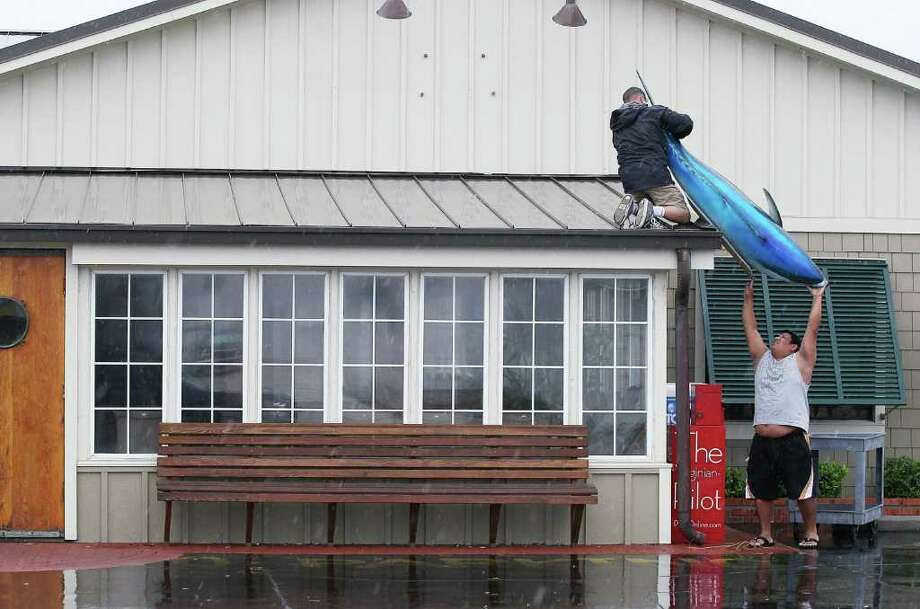 KILL DEVIL HILLS, NC - SEPTEMBER 03: Two men put a large fish back onto the front of a resturant after Hurricane Earl on September 3, 2010 in Kill Devil Hills, North Carolina. Hurricane Earl was downgraded to a category 2 before brushing the Outer Banks early Friday morning causing minimal damage.  (Photo by Mark Wilson/Getty Images) Photo: Mark Wilson, Getty Images / 2010 Getty Images