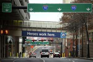 A Heroes work here sign hangs from the walkway connecting Yale New Haven Hospital to a parking garage in New Haven on December 4, 2020.