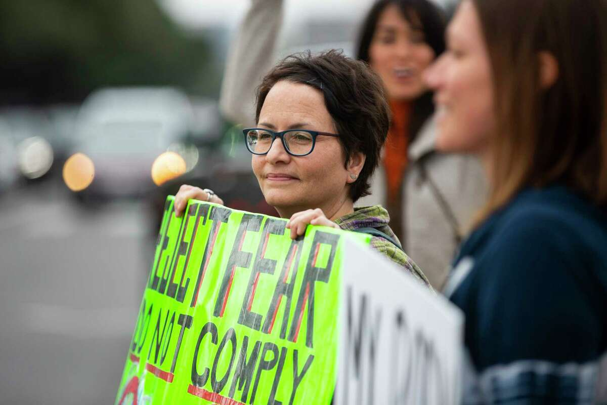Suzanna Simmonds holds a sign during the Rally for Covid-19 Liberty, Health, and Choice at the intersection of Westheimer and Post Oak on Saturday, Dec. 12, 2020.